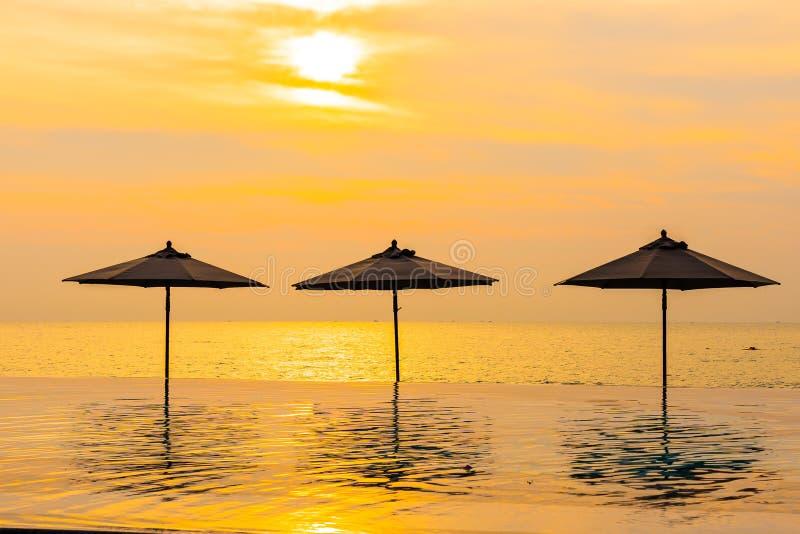 Regenschirm und Stuhl um Ozeanstrand des Swimmingpools neary Seezur Sonnenaufgang- oder Sonnenuntergangzeit stockfotos