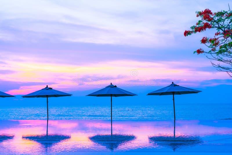 Regenschirm und Stuhl um Ozeanstrand des Swimmingpools neary Seezur Sonnenaufgang- oder Sonnenuntergangzeit stockbild