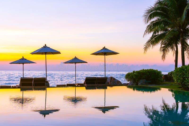 Regenschirm und Stuhl um Swimmingpool im Urlaubshotel f?r Freizeitreise und -ferien stockbild