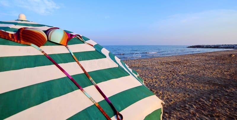 Regenschirme auf dem Sand mit einer Gewohnheit BRA lizenzfreies stockfoto