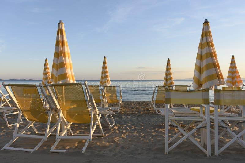 Regenschirme und Sonnenruhesessel bereit während der Sommersaison stockfotos
