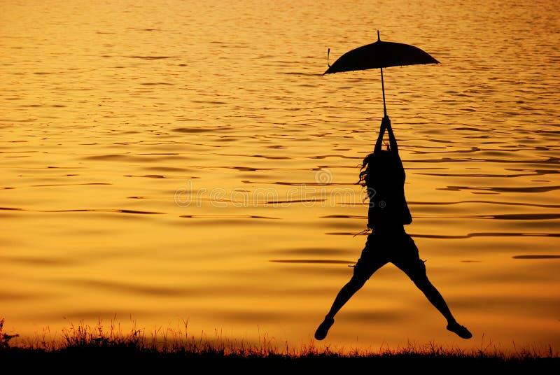 Regenschirmfrau springen und Sonnenuntergang im See lizenzfreie stockfotografie