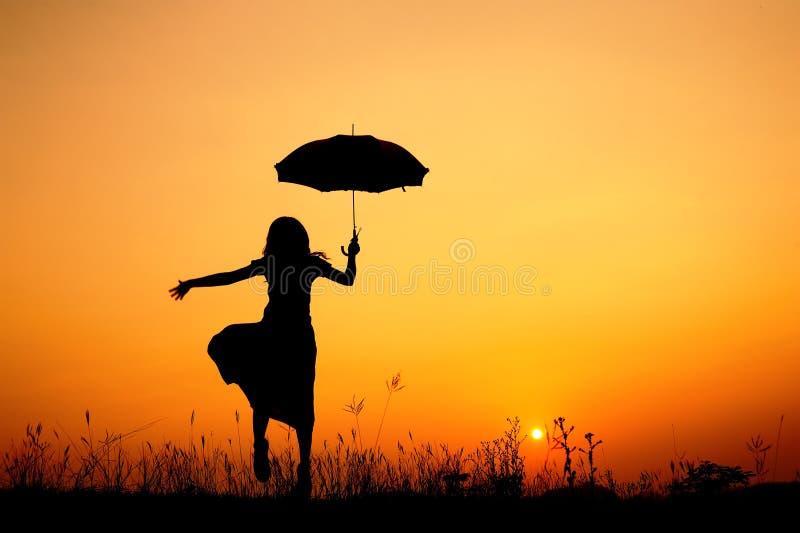 Regenschirmfrauen- und -sonnenuntergangschattenbild lizenzfreie stockbilder