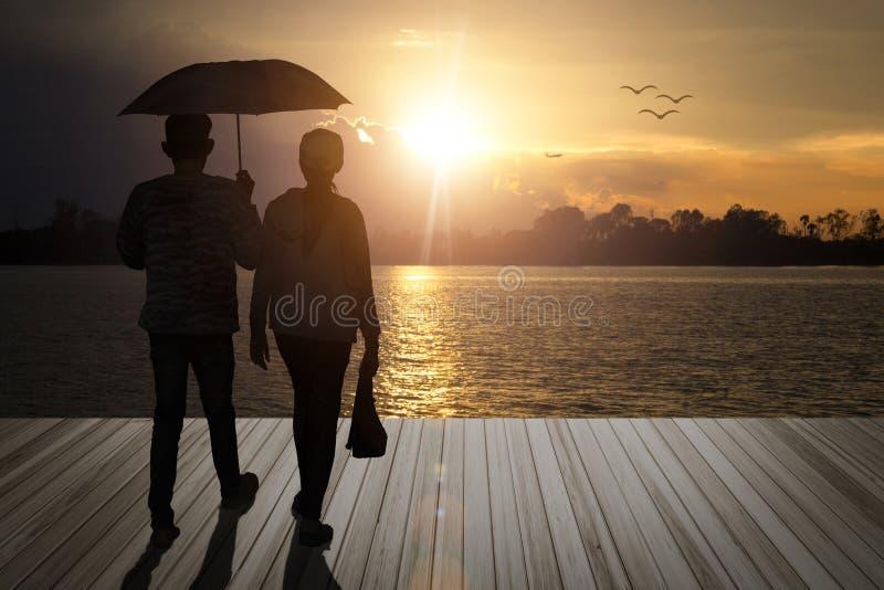 Regenschirmpaarholding geben Liebhaberweg auf hölzernen Balkonen, Klo lizenzfreies stockbild