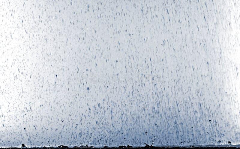 Regenstromen met plonsen op de oppervlakte van de vulklei stock fotografie
