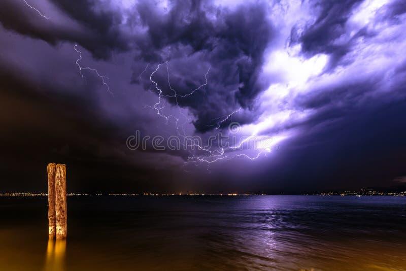 Regensturm mit Nachtblitzbolzen auf See garda lizenzfreie stockfotos