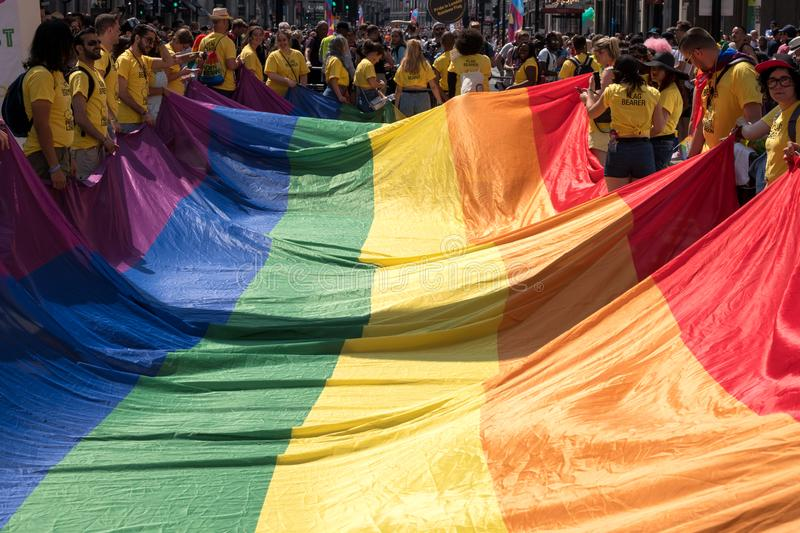 Close up of the giant rainbow LGBT flag at the front of the Gay Pride Parade in London 2018, with people holding the edges. royalty free stock photo