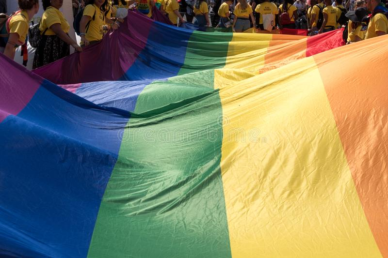 Close up of the giant rainbow LGBT flag at the front of the Gay Pride Parade in London 2018, with people holding the edges. royalty free stock images