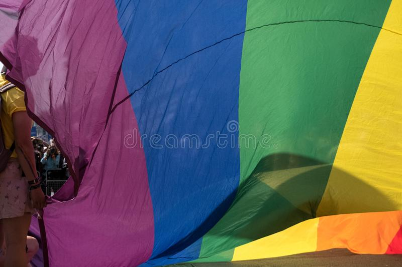 Woman holds up part of the giant rainbow flag at the London Pride Parade 2018. Woman`s face is hidden by the flag. stock image