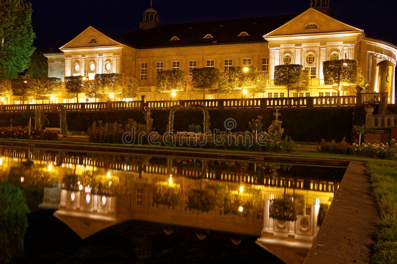 Lighted Baroque building water reflection night scene. The Neo-Baroque building Regentenbau by night, illuminated and reflected in the water of a fountain in the royalty free stock photo