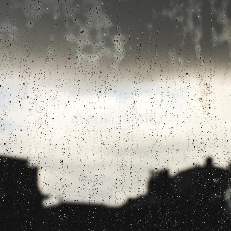 Regentröpfchen in einem Fenster stockbilder