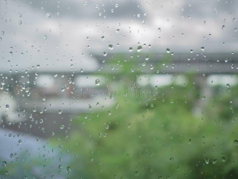 Regentropfen auf dem Fenster mit Unschärfefoto des Baums lizenzfreie stockbilder