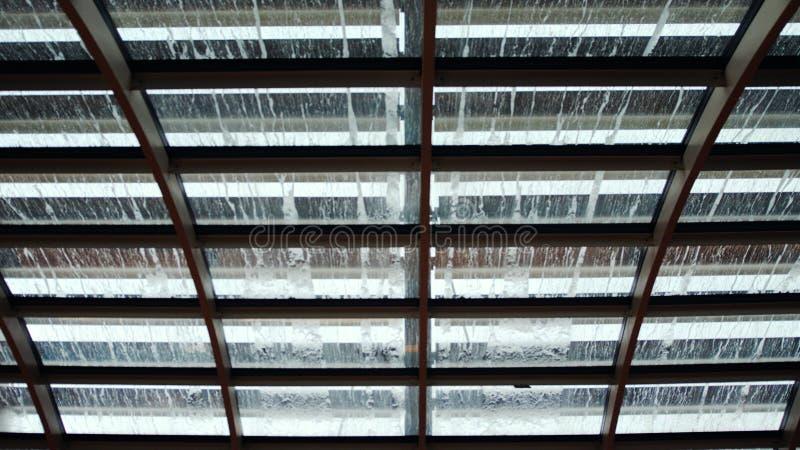 Regentropfen auf Glasdach Ansicht von der Unterseite auf Regentropfen spritzt und Fluss unten über das Glas blurry stockfoto