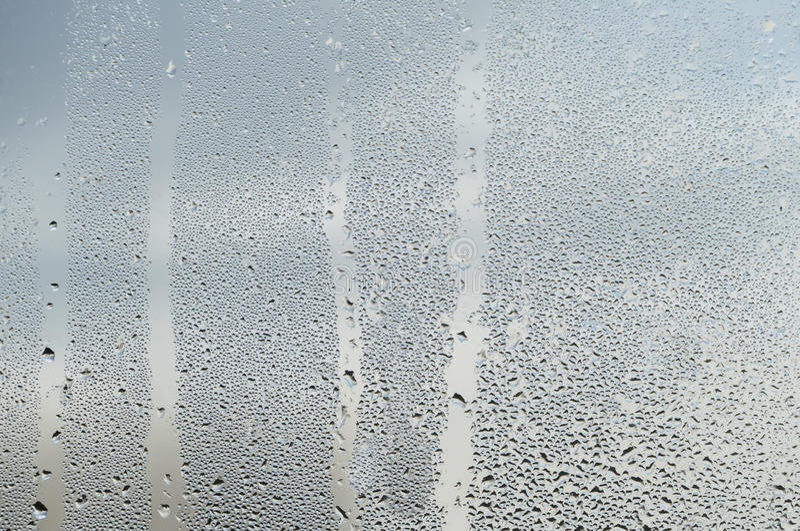 Regentropfen und Wasser-Läufe auf einer Glasfenster-Scheibe lizenzfreie stockbilder