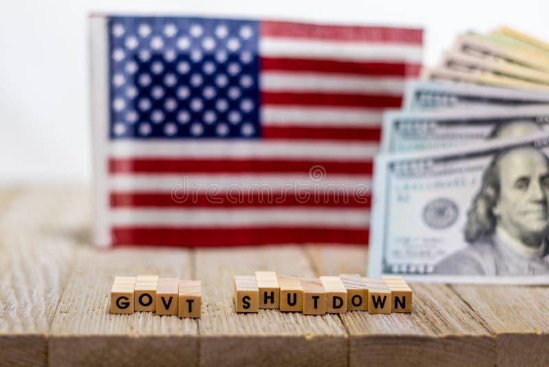 RegeringavstängningsUSA begrepp med amerikanska flaggan- och pengarräkningar på vit bakgrund och träbräde royaltyfria foton
