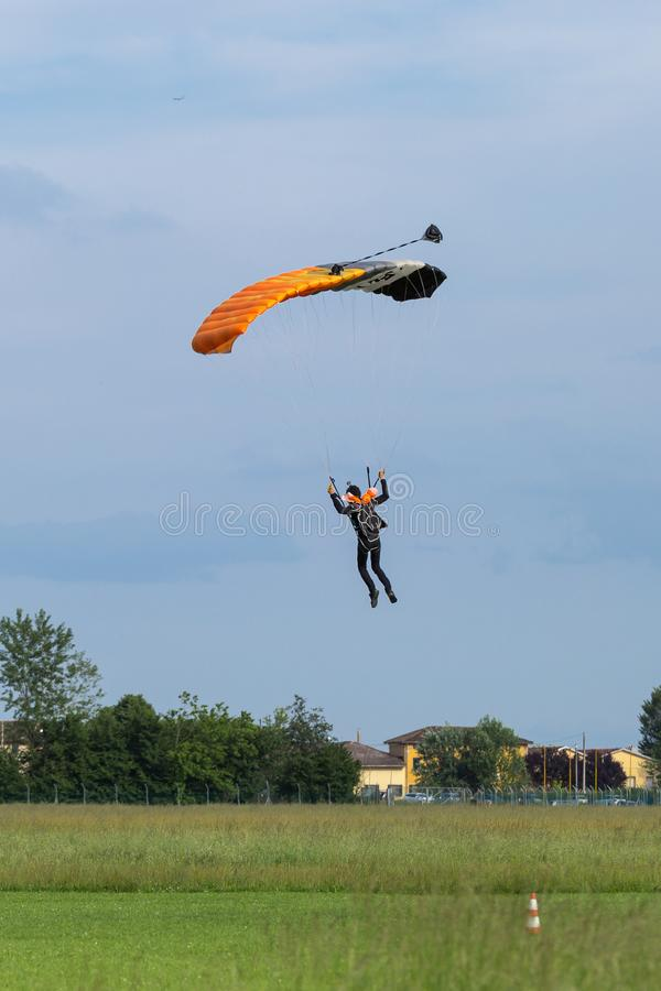 Reggio Emilia, Italien - Maj 2017: Fallskärmshopparen med apelsinen hoppa fallskärm mot klar blå himmel arkivfoton