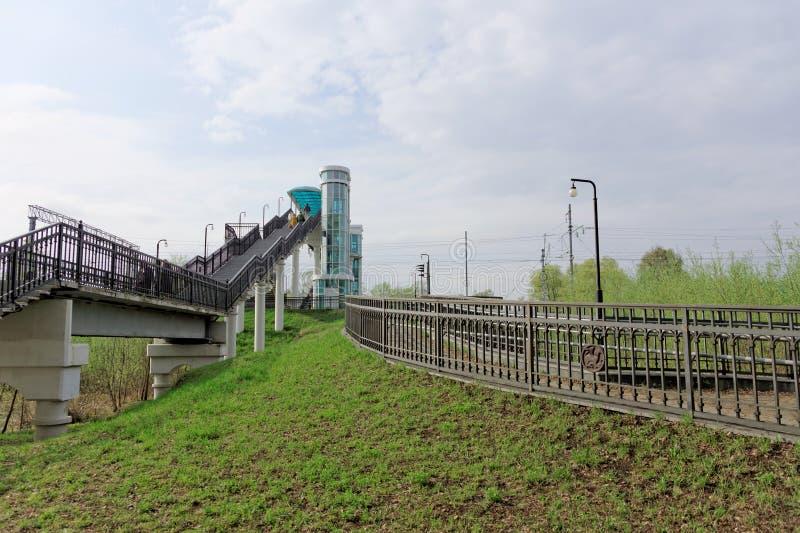 Região de Vladimir, Rússia - 6 de maio 2018 Cruzamento pedestre sobre as trilhas de estrada de ferro na estação de Bogolyubovo fotografia de stock royalty free