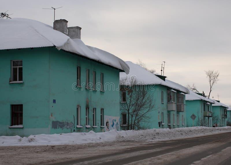 Região urbana das casas idênticas pequenas velhas a cidade de Ob ao longo da rua um dia de inverno cinzento, nublado foto de stock