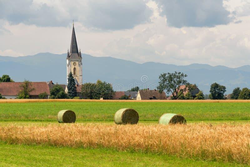 Región agrícola y pequeño pueblo con una iglesia, montañas austríacas en el fondo fotos de archivo