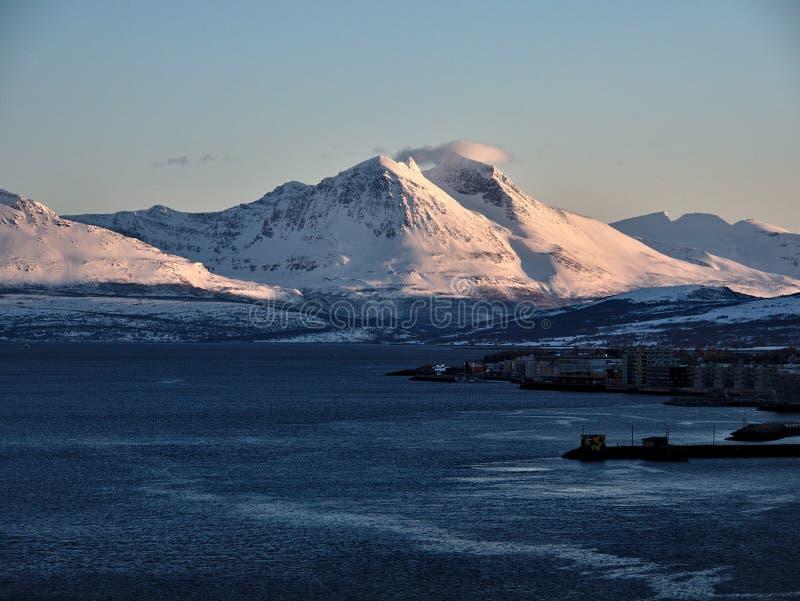 Región de Troms Costa rocosa del fiordo en invierno con nieve e hielo Montañas Nevado y pueblo pesquero en el fondo imágenes de archivo libres de regalías