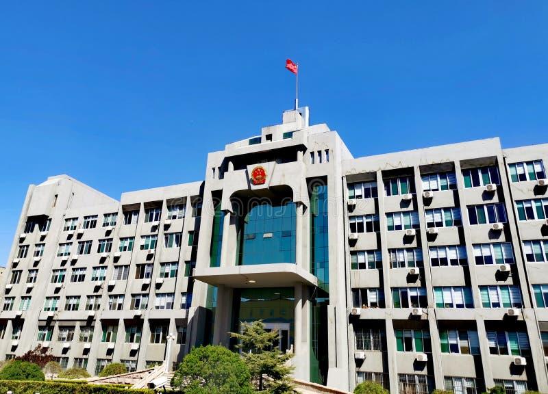 Regierungsgebäude mit Staatsflagge und Emblem @ China stockbild