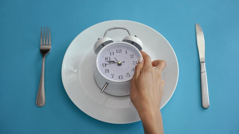 Daily regime, alarm clock on plate, adhere to diet time, proper nutrition stock image