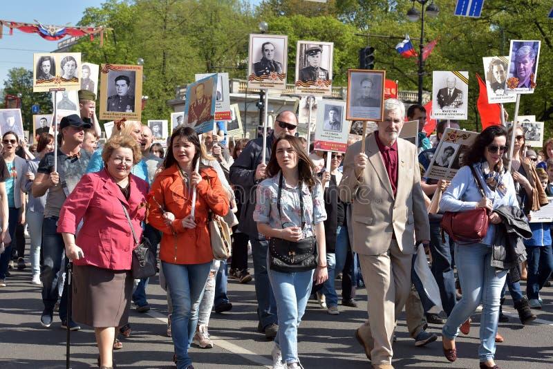 Regimiento inmortal - gente con los retratos de sus parientes, participantes en la Segunda Guerra Mundial, en el desfile de Victo fotografía de archivo libre de regalías