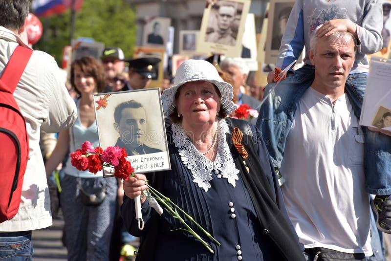 Regimiento inmortal - gente con los retratos de sus parientes, participantes en la Segunda Guerra Mundial, en el desfile de Victo fotos de archivo