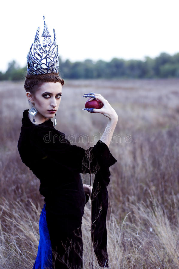 Regina diabolica con una mela fotografie stock