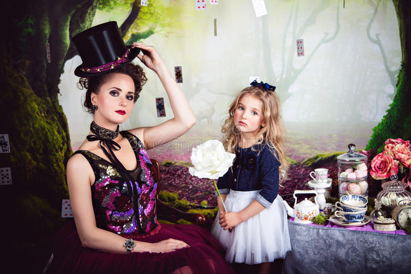 Regina diabolica ed Alice che tengono la rosa di bianco immagine stock libera da diritti