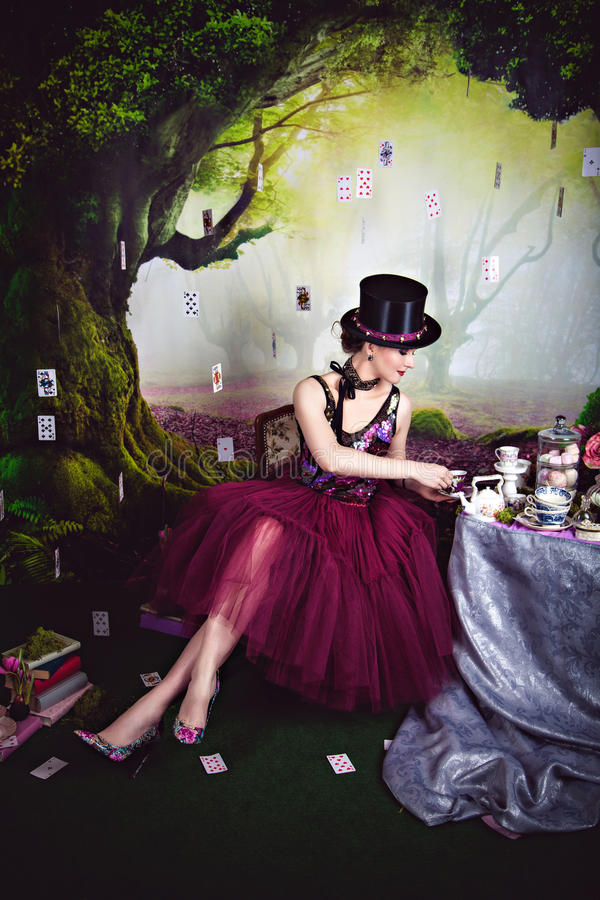 Regina diabolica in giocatore di bocce che si siede vicino alla tavola di tè immagine stock libera da diritti