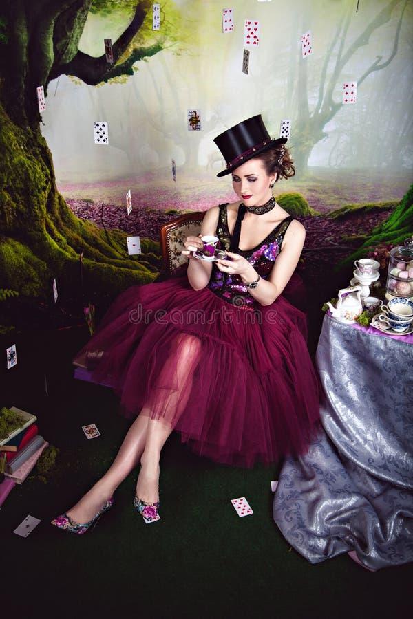 Regina diabolica in giocatore di bocce e tazza di tè vicino alla tavola immagine stock
