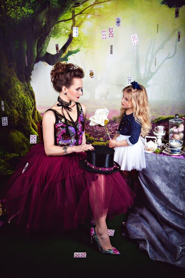 Regina ed Alice diaboliche con la rosa di bianco immagine stock