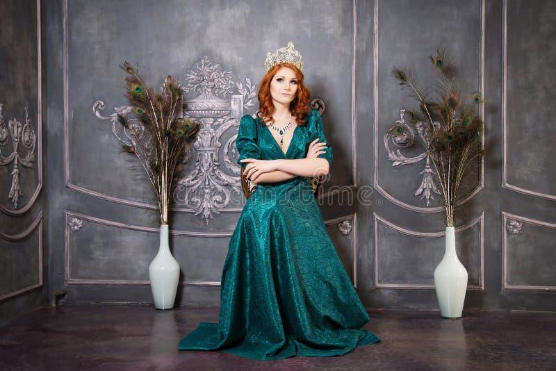 Regina, persona reale con la corona, capelli rossi e vestito verde fotografie stock