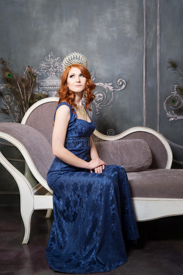 Regina, persona reale con la corona, capelli rossi in vestito viola blu fotografia stock