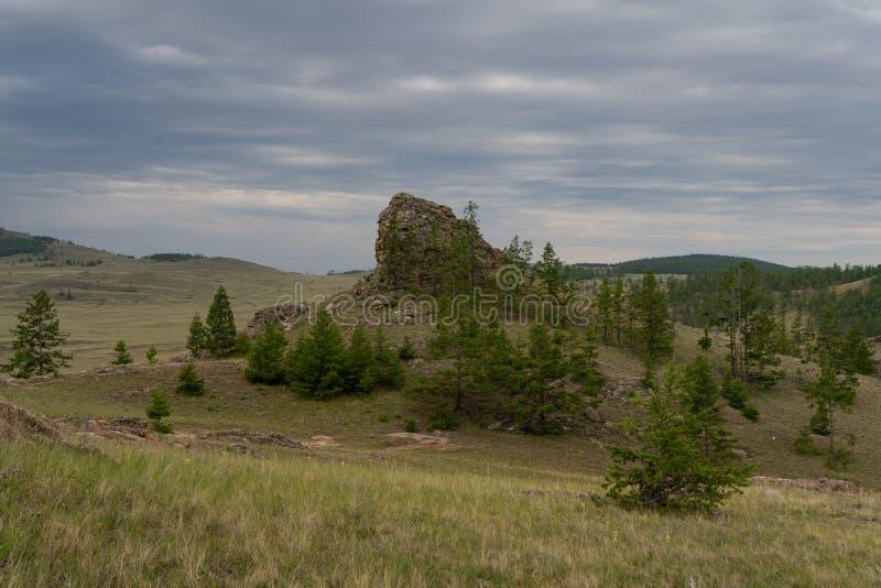 Regio Baikal Vuile weg op de Tazheranskaya-steppe bij de stenen stenen stenen rotsen, de Valley van de Stone Spirits genaamd stock foto's