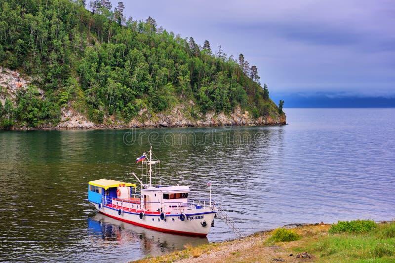 REGION des BAIKALSEES, IRKUTSK, RUSSLAND - Juli, 28 2016: Baikal-Landschaft mit einer gehenden Yacht auf Ufer der kleinen Bucht stockfotografie