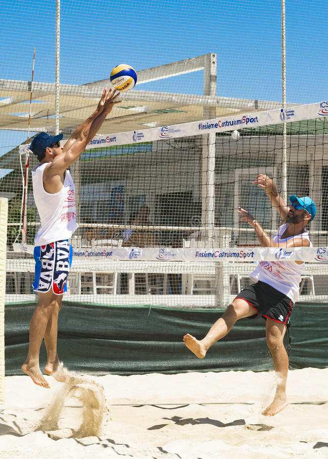 Regional beach volleyball tournament. Collision in the penalty while competing victory point to the sea with the participation of the band rum by presenting stock photography