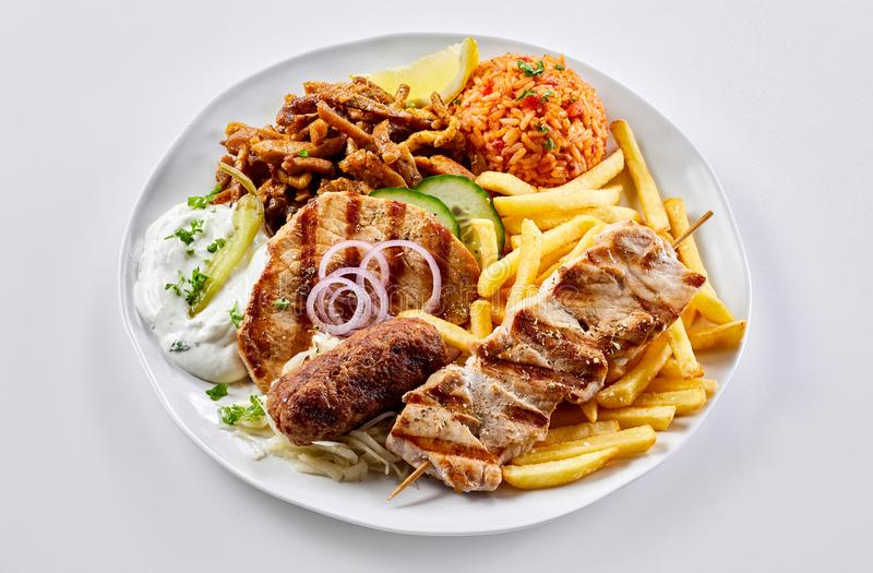 Regional Greek mixed grill with chips and pilaf royalty free stock photos