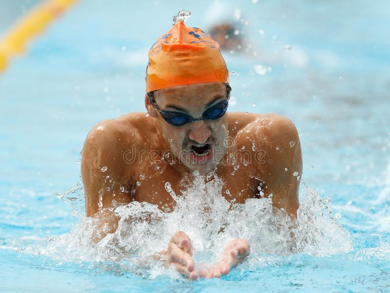Regional swimming team training session breaststroke style. A boy swims breaststroke during his training session in public local pool in the Spanish island of royalty free stock photography