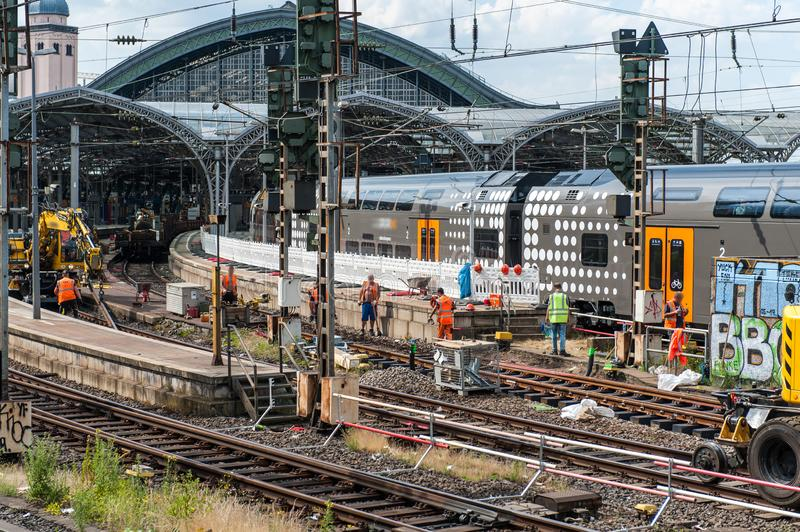 Regional train incoming in station in Cologen / Germany while workers build new rail tracks. In Juni 2019 stock photos