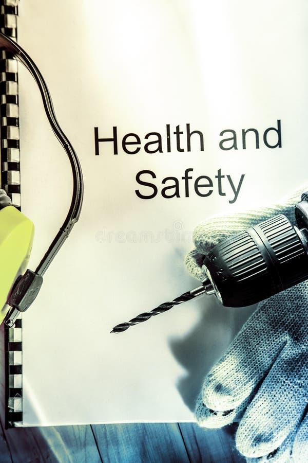 Register met beschermende brillen, boor en oortelefoons stock foto