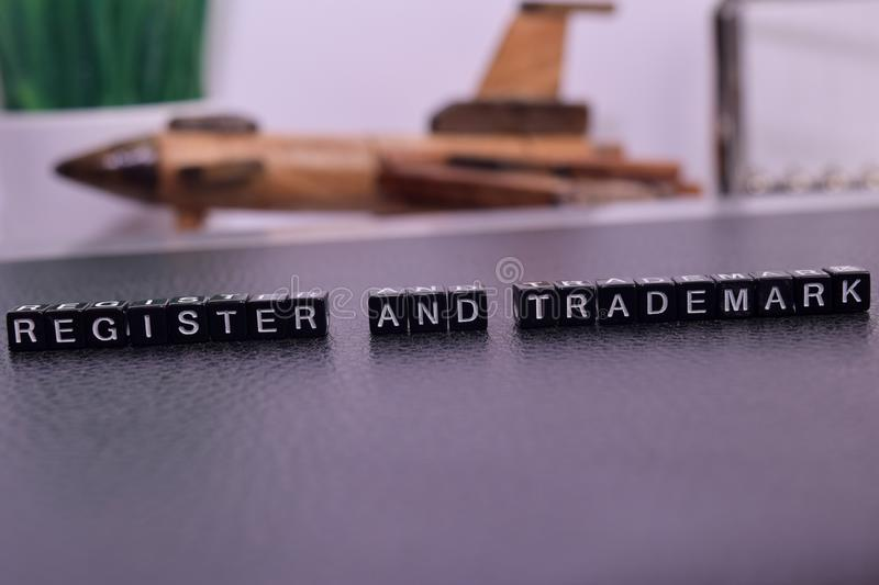 Register and Trademark on wooden blocks. Cross processed image with business concept on White background stock image