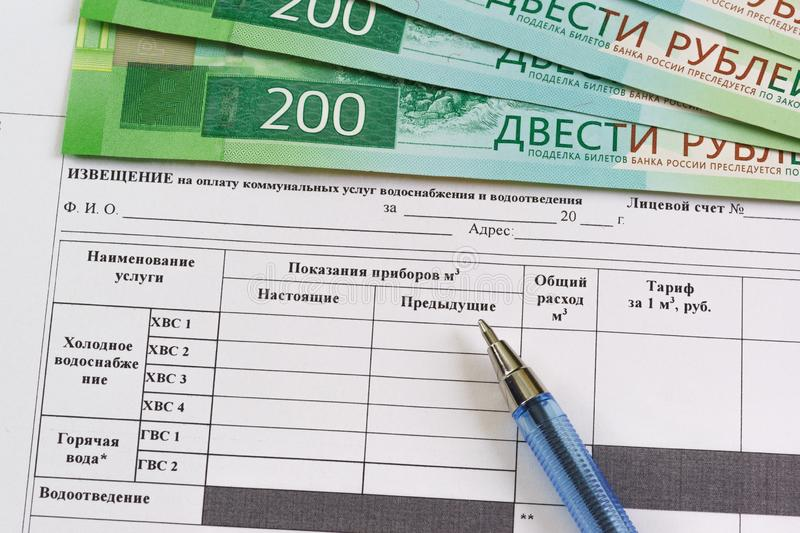 Registration of the receipt in Russian for payment for the consumed water and new banknotes of 200 rubles. Calculation of utilities stock photo