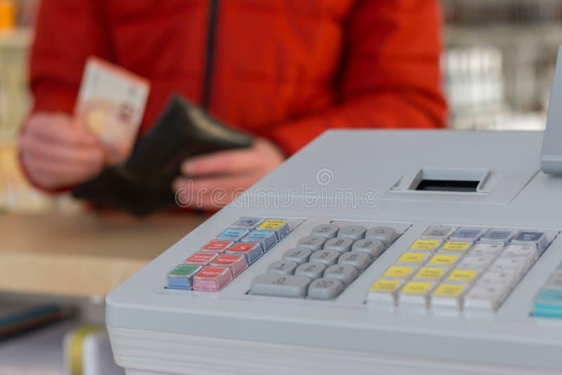 Registratore di cassa in un deposito: Il cliente sta pagando immagine stock