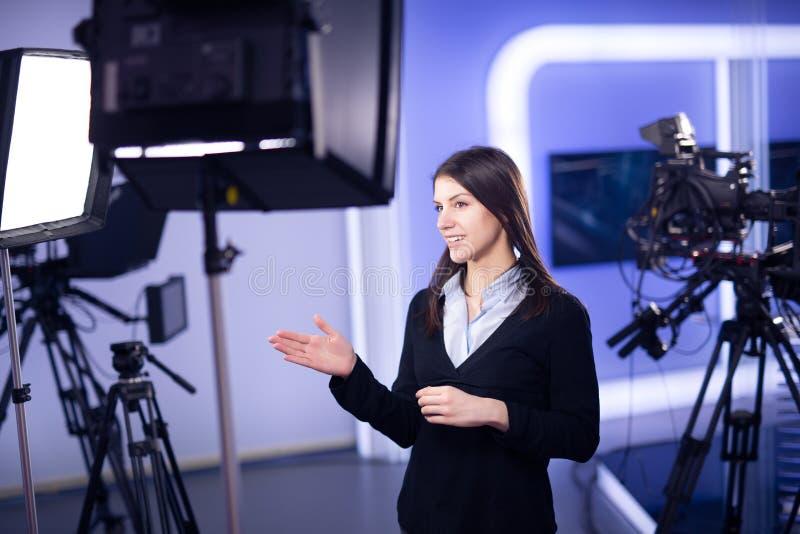 Registrazione del relatore della televisione nello studio di notizie Ancora femminile del giornalista che presenta relazione di a immagini stock