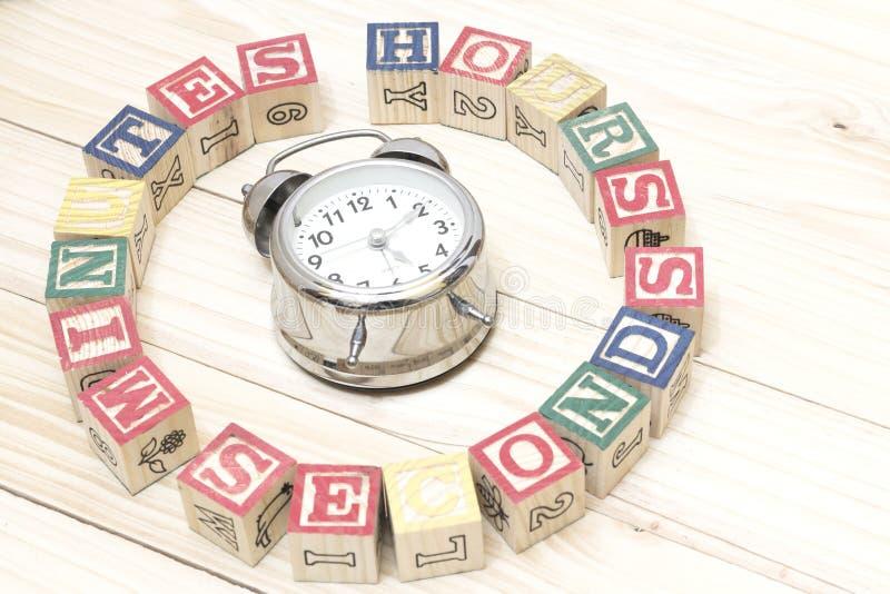 Registre con los cubos de madera en las horas de madera de las palabras de la tabla, minutos, segundos se refrescan imagenes de archivo