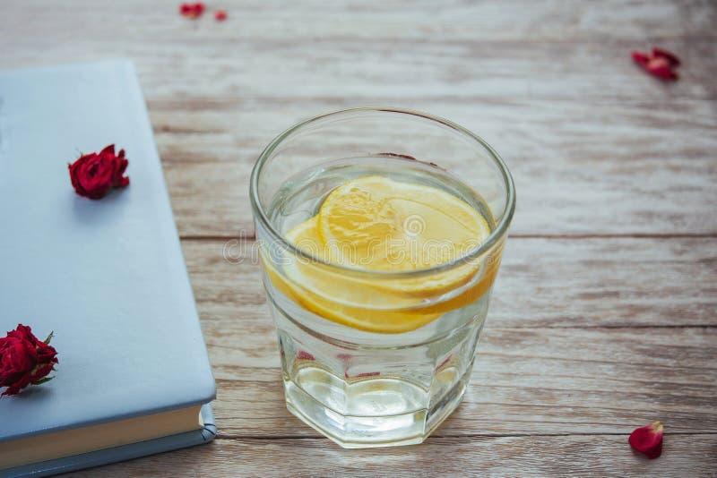 registre o vidro dos vidros e das pétalas da flor da água com limão fotografia de stock