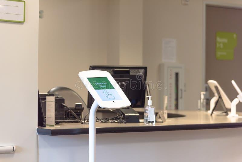 Registre a tabuleta do quiosque na recepção do teste de diagnóstico imagens de stock royalty free