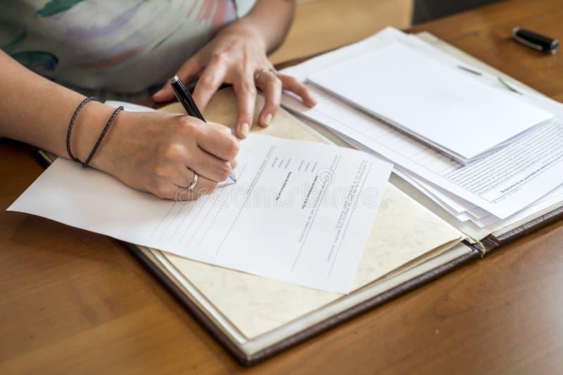 Registro de firma de la novia de la boda, pluma de tenencia y pares elegantes de la boda del documento oficial imágenes de archivo libres de regalías